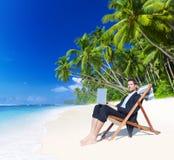 Επιχειρηματίας που εργάζεται με το lap-top στην παραλία Στοκ εικόνα με δικαίωμα ελεύθερης χρήσης