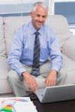 Επιχειρηματίας που εργάζεται με το lap-top του και που χαμογελά στη κάμερα Στοκ φωτογραφίες με δικαίωμα ελεύθερης χρήσης