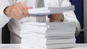 Επιχειρηματίας που εργάζεται σε ένα γραφείο και που συσσωρεύει τα βιβλία απόθεμα βίντεο