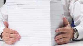 Επιχειρηματίας που εργάζεται σε ένα γραφείο και που συσσωρεύει τα βιβλία φιλμ μικρού μήκους