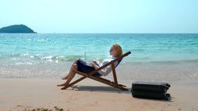 Επιχειρηματίας που εργάζεται σε ένα lap-top καθμένος σε έναν αργόσχολο θαλασσίως σε μια άσπρη αμμώδη παραλία ανεξάρτητος ή workah στοκ εικόνες με δικαίωμα ελεύθερης χρήσης