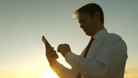 Επιχειρηματίας που εργάζεται στην ταμπλέτα στο ηλιοβασίλεμα στο πάρκο εργασίες γεωπόνων με την ταμπλέτα στον τομέα αγρότης στη φυ απόθεμα βίντεο