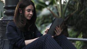 Επιχειρηματίας που εργάζεται στην ταμπλέτα στο βοτανικό κήπο, σταθμός τρένου Μαδρίτη Atocha απόθεμα βίντεο
