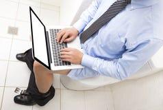 Επιχειρηματίας που εργάζεται στην τουαλέτα με το lap-top Στοκ φωτογραφία με δικαίωμα ελεύθερης χρήσης