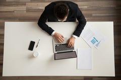 Επιχειρηματίας που εργάζεται στη συνεδρίαση φορητών προσωπικών υπολογιστών στο γραφείο, τοπ άποψη Στοκ Εικόνες