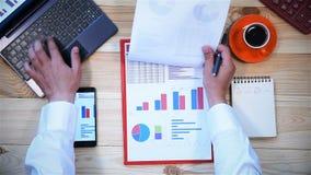 Επιχειρηματίας που εργάζεται στις οικονομικές εκθέσεις φιλμ μικρού μήκους