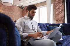 Επιχειρηματίας που εργάζεται στον καναπέ στο σύγχρονο δημιουργικό γραφείο Στοκ φωτογραφία με δικαίωμα ελεύθερης χρήσης