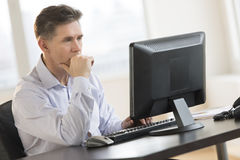 Επιχειρηματίας που εργάζεται στον προσωπικό υπολογιστή γραφείου στην αρχή Στοκ Φωτογραφίες