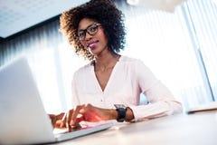 Επιχειρηματίας που εργάζεται στον υπολογιστή και το χαμόγελό της Στοκ φωτογραφία με δικαίωμα ελεύθερης χρήσης