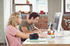 Επιχειρηματίας που εργάζεται στον υπολογιστή με το συνάδελφο στην αρχή Στοκ Εικόνες