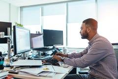 Επιχειρηματίας που εργάζεται στον υπολογιστή στο γραφείο του στην αρχή Στοκ φωτογραφίες με δικαίωμα ελεύθερης χρήσης