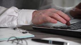 Επιχειρηματίας που εργάζεται στο έγγραφο και που δακτυλογραφεί στο lap-top, κινηματογράφηση σε πρώτο πλάνο φιλμ μικρού μήκους