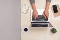 Επιχειρηματίας που εργάζεται στο γραφείο γραφείων και που χρησιμοποιεί το lap-top, τοπ άποψη Στοκ Φωτογραφίες