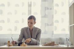 Επιχειρηματίας που εργάζεται στο γραφείο γραφείων που γράφει στο σημειωματάριο Στοκ εικόνες με δικαίωμα ελεύθερης χρήσης