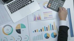 Επιχειρηματίας που εργάζεται στο γραφείο γραφείων στο lap-top και τις οικονομικές εκθέσεις του Τοπ όψη φιλμ μικρού μήκους
