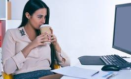 Επιχειρηματίας που εργάζεται στο γραφείο στο γραφείο, εξετάζοντας το όργανο ελέγχου υπολογιστών, που κρατά το φλιτζάνι του καφέ σ Στοκ Εικόνες