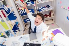 Επιχειρηματίας που εργάζεται στο γραφείο με τους σωρούς των βιβλίων και των εγγράφων Στοκ Φωτογραφία