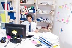 Επιχειρηματίας που εργάζεται στο γραφείο με τους σωρούς των βιβλίων και των εγγράφων Στοκ Εικόνα
