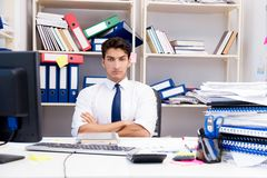 Επιχειρηματίας που εργάζεται στο γραφείο με τους σωρούς των βιβλίων και των εγγράφων Στοκ Φωτογραφίες