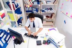 Επιχειρηματίας που εργάζεται στο γραφείο με τους σωρούς των βιβλίων και των εγγράφων Στοκ φωτογραφίες με δικαίωμα ελεύθερης χρήσης
