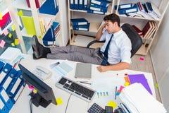 Επιχειρηματίας που εργάζεται στο γραφείο με τους σωρούς των βιβλίων και των εγγράφων Στοκ Εικόνες