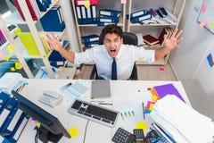 Επιχειρηματίας που εργάζεται στο γραφείο με τους σωρούς των βιβλίων και των εγγράφων Στοκ φωτογραφία με δικαίωμα ελεύθερης χρήσης