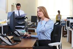 Επιχειρηματίας που εργάζεται στο γραφείο που πάσχει από τον πόνο λαιμών Στοκ εικόνες με δικαίωμα ελεύθερης χρήσης