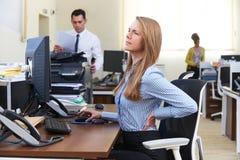 Επιχειρηματίας που εργάζεται στο γραφείο που πάσχει από τον πόνο στην πλάτη Στοκ φωτογραφία με δικαίωμα ελεύθερης χρήσης