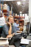Επιχειρηματίας που εργάζεται στο γραφείο στην αποθήκη εμπορευμάτων Στοκ εικόνα με δικαίωμα ελεύθερης χρήσης