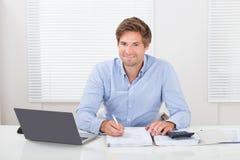 Επιχειρηματίας που εργάζεται στο γραφείο στην αρχή Στοκ εικόνες με δικαίωμα ελεύθερης χρήσης