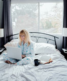 Επιχειρηματίας που εργάζεται στο κρεβάτι Στοκ φωτογραφία με δικαίωμα ελεύθερης χρήσης