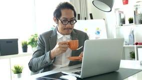 Επιχειρηματίας που εργάζεται στο φορητό προσωπικό υπολογιστή στο γραφείο, 4K σε αργή κίνηση ασιατικό επιχειρησιακό άτομο που φορά φιλμ μικρού μήκους