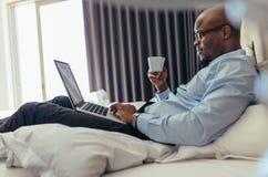 Επιχειρηματίας που εργάζεται στο φορητό προσωπικό υπολογιστή που βρίσκεται στο κρεβάτι Στοκ Φωτογραφία