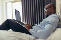 Επιχειρηματίας που εργάζεται στο φορητό προσωπικό υπολογιστή που βρίσκεται στο κρεβάτι Στοκ φωτογραφίες με δικαίωμα ελεύθερης χρήσης