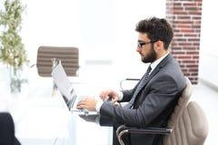 Επιχειρηματίας που εργάζεται στο φωτεινό γραφείο, που κάθεται στο γραφείο στοκ φωτογραφία με δικαίωμα ελεύθερης χρήσης