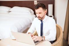 Επιχειρηματίας που εργάζεται στο δωμάτιο ξενοδοχείου του Στοκ Φωτογραφία