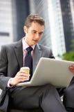 Επιχειρηματίας που εργάζεται στο lap-top έξω από το γραφείο Στοκ Εικόνα