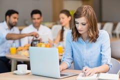 Επιχειρηματίας που εργάζεται στο lap-top ενώ έχοντας τον καφέ Στοκ Εικόνες