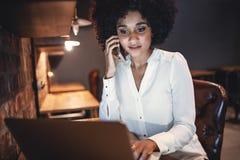 Επιχειρηματίας που εργάζεται στο lap-top και που μιλά στο κινητό τηλέφωνο στο γ Στοκ εικόνες με δικαίωμα ελεύθερης χρήσης