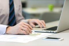 Επιχειρηματίας που εργάζεται στο lap-top και τα τυπωμένα διαγράμματα Στοκ Φωτογραφία