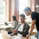 Επιχειρηματίας που εργάζεται στο lap-top, που μιλά στο συνάδελφο σε ομο -ομο-workin στοκ εικόνες με δικαίωμα ελεύθερης χρήσης