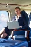 Επιχειρηματίας που εργάζεται στο lap-top στην καμπίνα ελικοπτέρων κατά τη διάρκεια Fligh Στοκ Εικόνες