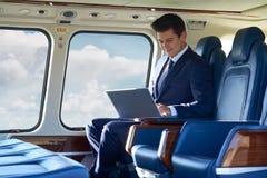 Επιχειρηματίας που εργάζεται στο lap-top στην καμπίνα ελικοπτέρων κατά τη διάρκεια της πτήσης Στοκ φωτογραφία με δικαίωμα ελεύθερης χρήσης
