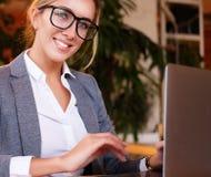 Επιχειρηματίας που εργάζεται στο lap-top στη καφετερία Η νέα επιχειρησιακή γυναίκα χρησιμοποιεί το lap-top στον καφέ Στοκ εικόνα με δικαίωμα ελεύθερης χρήσης