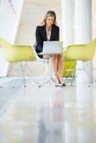Επιχειρηματίας που εργάζεται στο lap-top στον πίνακα στο σύγχρονο γραφείο Στοκ φωτογραφία με δικαίωμα ελεύθερης χρήσης