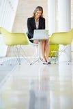 Επιχειρηματίας που εργάζεται στο lap-top στον πίνακα στο σύγχρονο γραφείο Στοκ Φωτογραφία