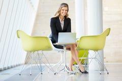 Επιχειρηματίας που εργάζεται στο lap-top στον πίνακα στο σύγχρονο γραφείο Στοκ Εικόνα