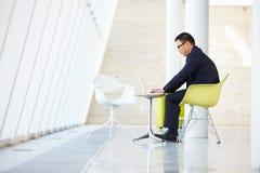 Επιχειρηματίας που εργάζεται στο lap-top στον πίνακα στο σύγχρονο γραφείο Στοκ Φωτογραφίες