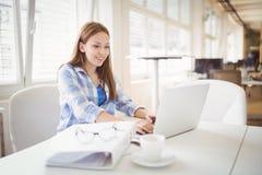 Επιχειρηματίας που εργάζεται στο lap-top στο γραφείο στο δημιουργικό γραφείο Στοκ Εικόνα