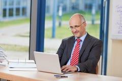 Επιχειρηματίας που εργάζεται στο lap-top στο γραφείο Στοκ Φωτογραφίες